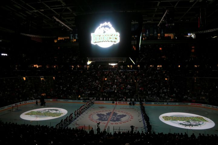 The logo of the Humboldt Broncos is displayed on the ice and scoreboard during a moment silence before a game between the Mon