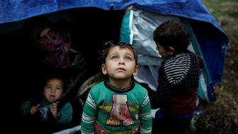 "A Syrian refugee boy stands in front of his family tent at a makeshift camp for refugees and migrants next to the Moria camp on the island of Lesbos, Greece, November 30, 2017. REUTERS/Alkis Konstantinidis   SEARCH ""MORIA CAMP"" FOR THIS STORY. SEARCH ""WIDER IMAGE"" FOR ALL STORIES."