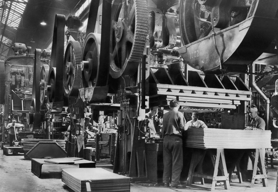 Workers in a factory operate a row of huge mechanical presses circa 1935.
