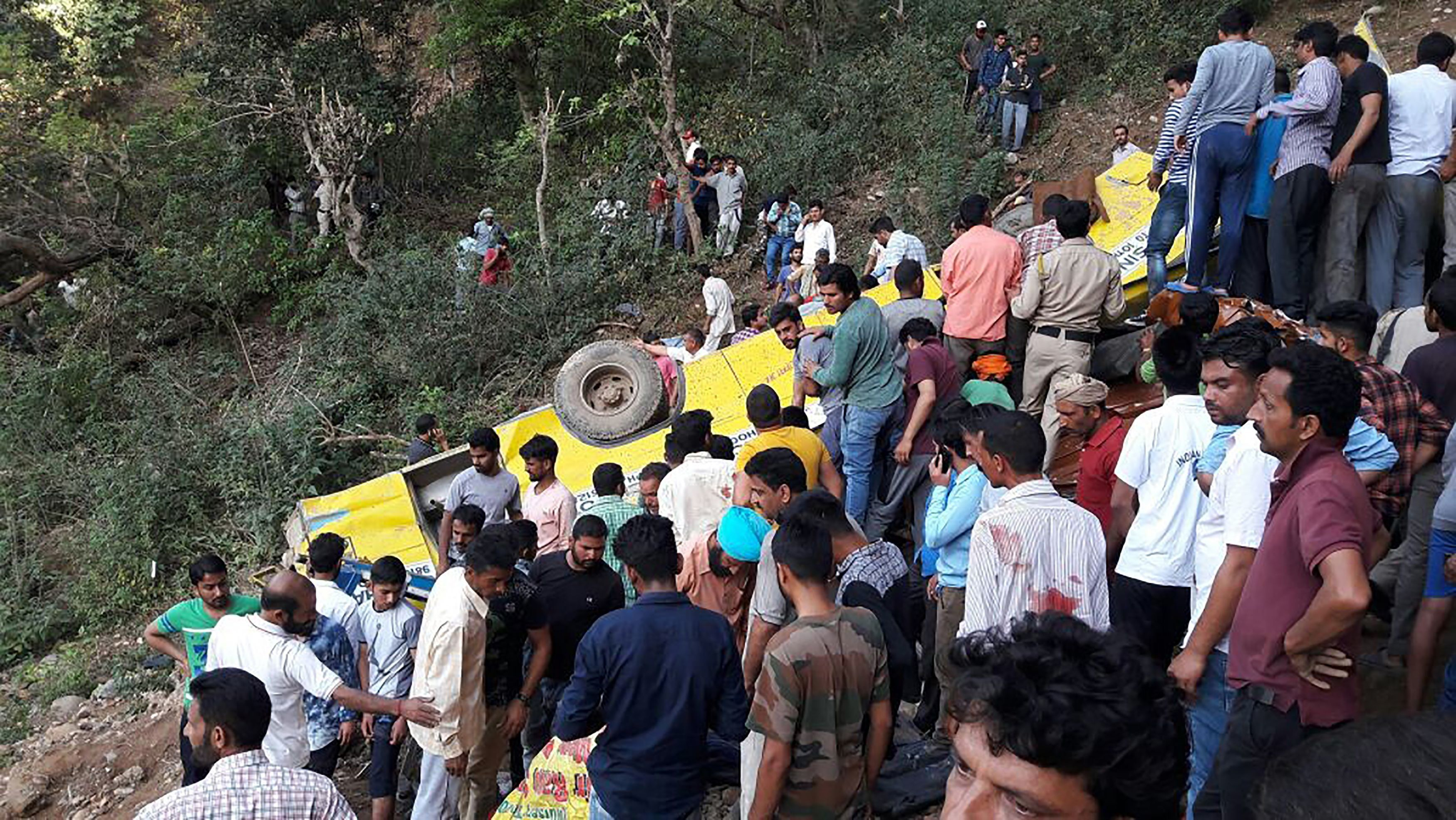 People help to rescue injured after a private school bus falls into a deep gorge in Nurpur, Kangra district, in India on Apri