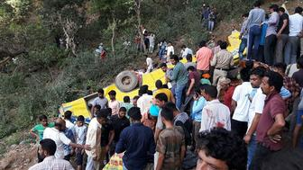 Indian people helping to rescue injured after a private school bus falls into a deep gorge in Nurpur, Kangra district, on April 9, 2018. At least 30 people, including 27 children, were killed on April 9 in northern India's Himachal Pradesh state when a schoolbus plunged off a cliff, police said. / AFP PHOTO / -        (Photo credit should read -/AFP/Getty Images)