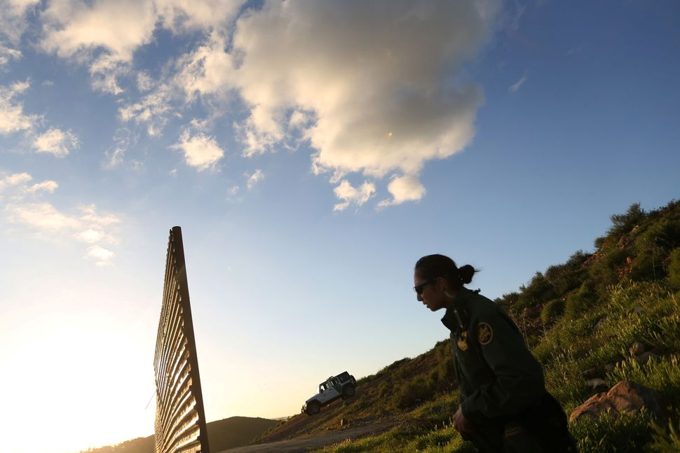 An officer of the U.S. Border Patrol inspects the area where the border fence separating Mexico and the U.S. is interrupted o