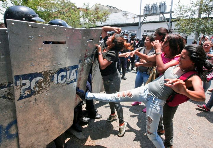 Families clashed with security forces outside the police station in Valencia, Venezuela, where nearly 70 prisoners died in a