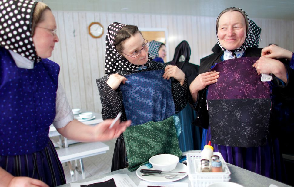 Hutterite women choose fabric to sew into garments.