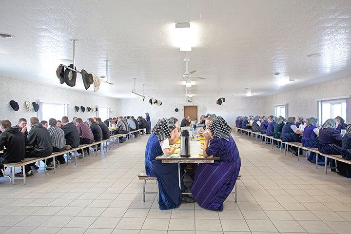 Members of a Hutterite colony eat a communal dinner segregated by gender.