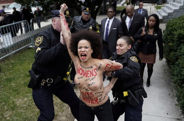 Protester Nicolle Rochelle is subdued by police after breaking through the barriers as Cosby arrived...