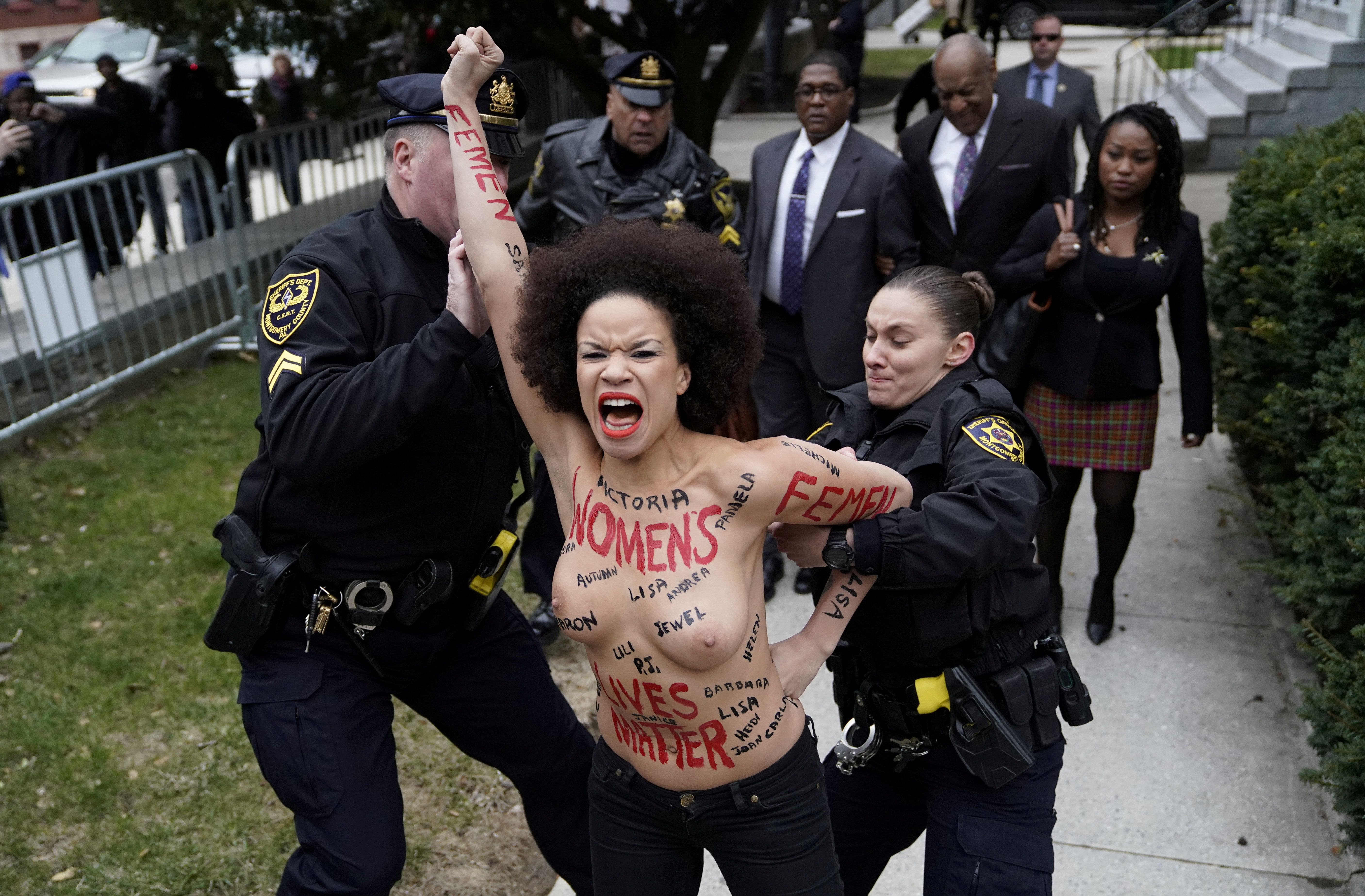 Protester Nicolle Rochelle is subdued by police after breaking through the barriers as Cosby arrived on his first day of his