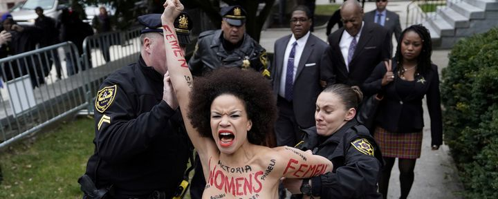 Police hold back protester Nicolle Rochelle in front of the Montgomery County Courthouse in Norristown, Pennsylvania, on Apri