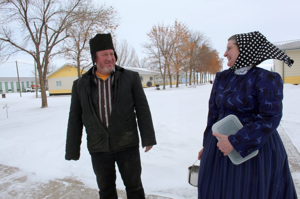 Hutterite women wear patterned head coverings.