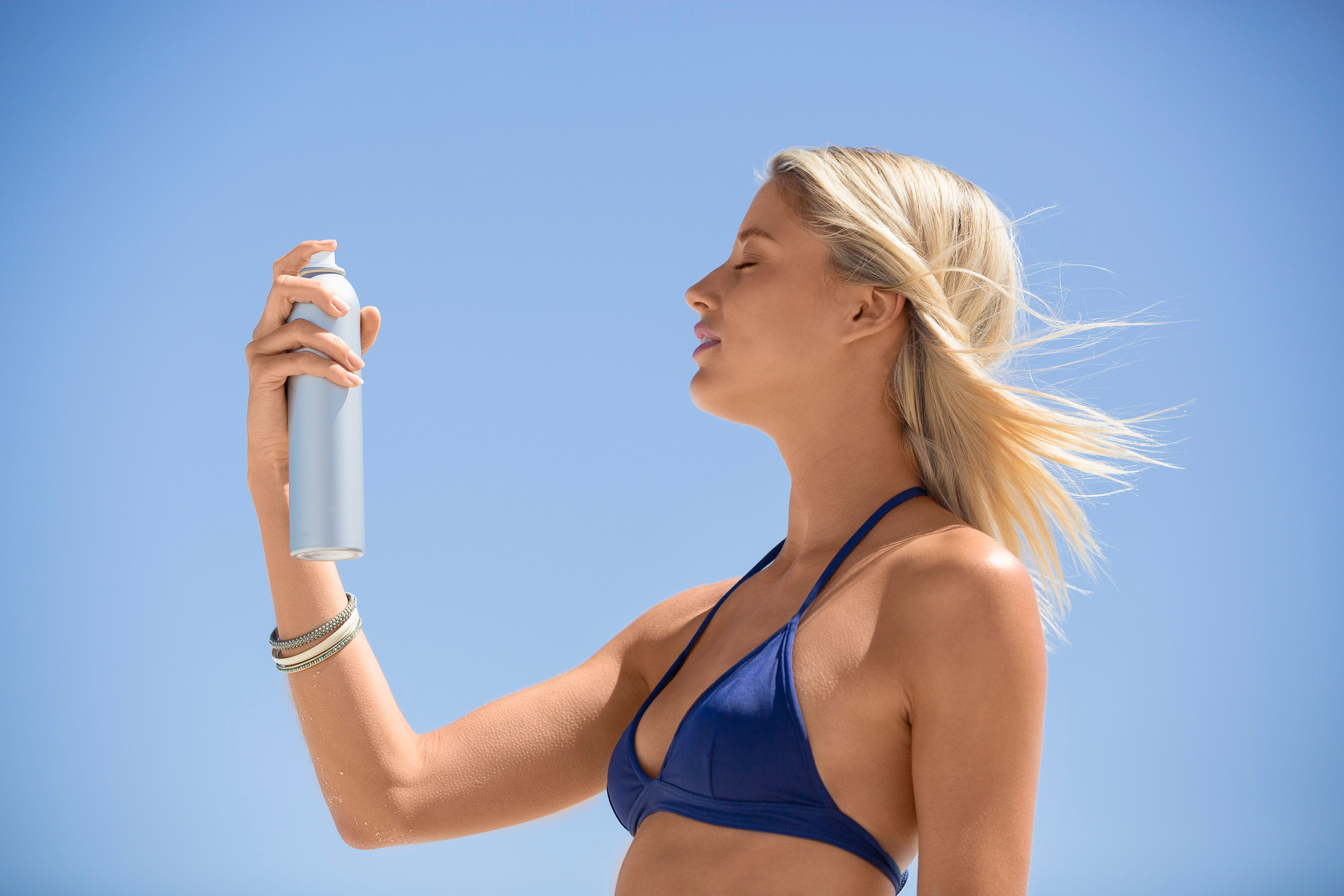 Woman spraying sunscreen on her face