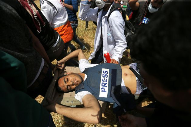 Mortally wounded Palestinian journalist Yasser Murtaja is evacuated during clashes at the Israel-Gaza...