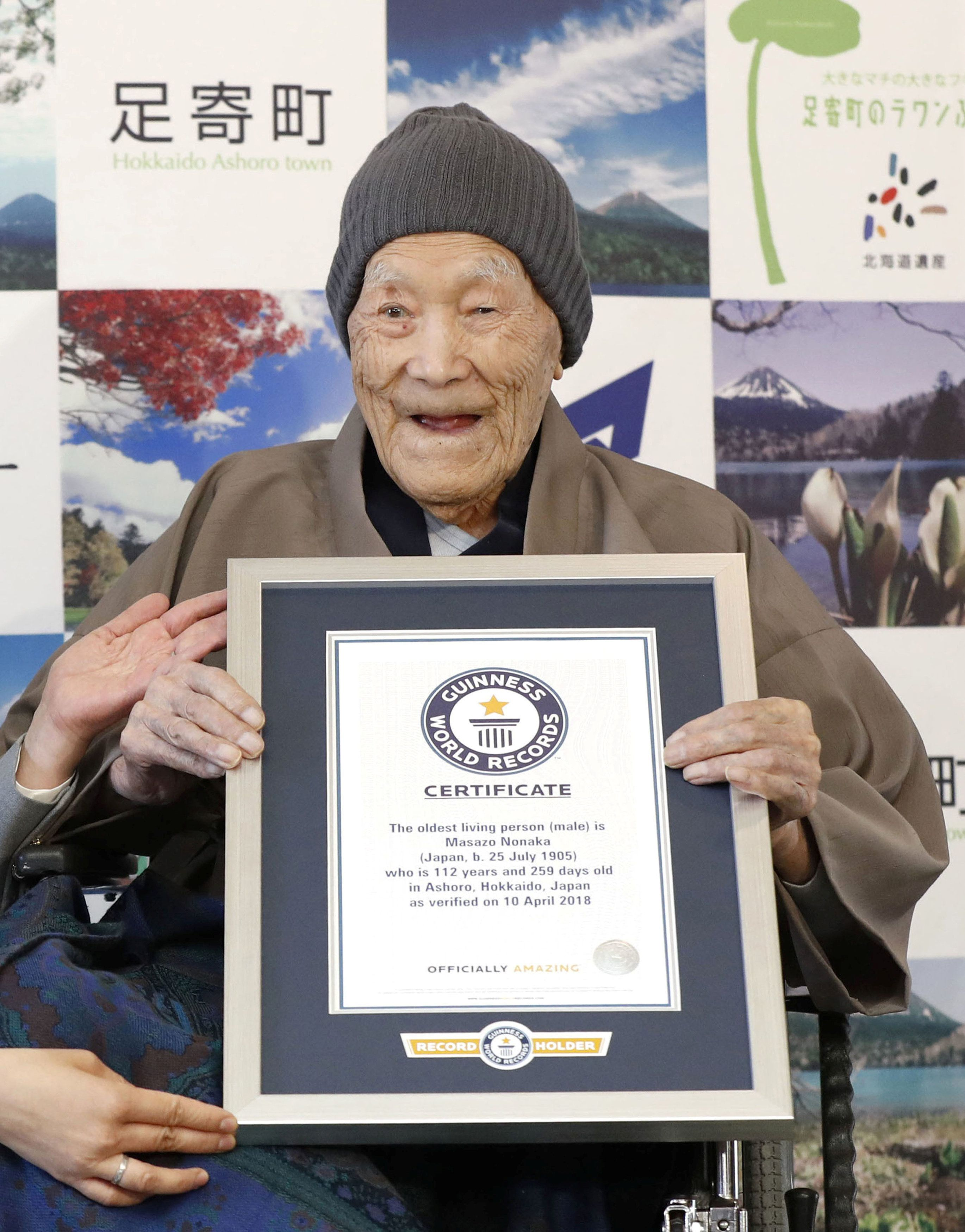 Masazo Nonaka, who was born 112 years and 259 days ago, receives a Guinness World Records certificate naming him the world's