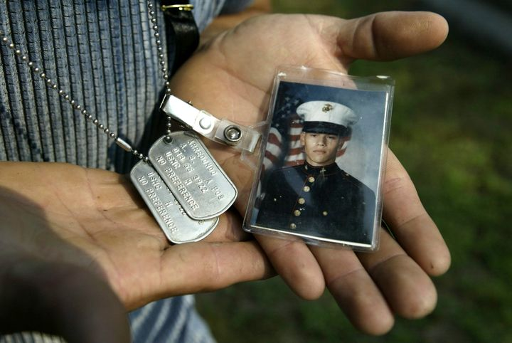 Carlos Arredondo holds dog tags that belonged to his son, Lance Cpl. Alexander Scott Arredondo, while visiting his grave