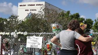 PARKLAND, FL - FEBRUARY 23:  Margarita Lasalle (R), the budget keeper, and Joellen Berman, Guidance Data Specialist, look on at the memorial in front of Marjory Stoneman Douglas High School as teachers and staff are allowed to return to the school for the first time since the mass shooting on campus on February 23, 2018 in Parkland, Florida. Police arrested 19-year-old former student Nikolas Cruz for killing 17 people at the high school.  (Photo by Joe Raedle/Getty Images)