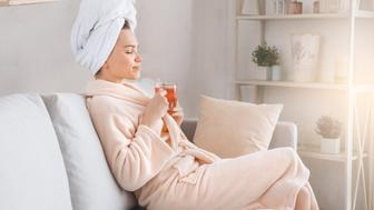 Young female body care at home drinking tea