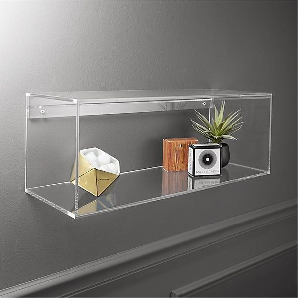 """If you keep your seating against a wall, <a href=""""https://www.cb2.com/acrylic-storage-shelf/s215620"""" target=""""_blank"""">floating"""