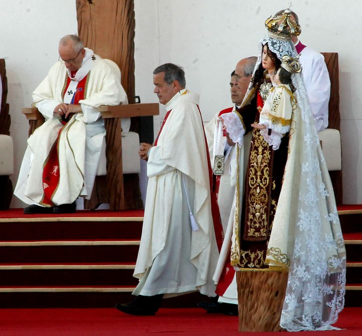 The bishop of Osorno, Juan Barros (center), takes part in an open-air mass celebrated by Pope Francis (left) at Maquehue airp