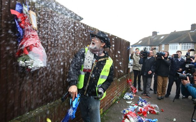 Iain Gordon pulls the flowers down from a fence opposite the house of Richard Osborn-Brooks last