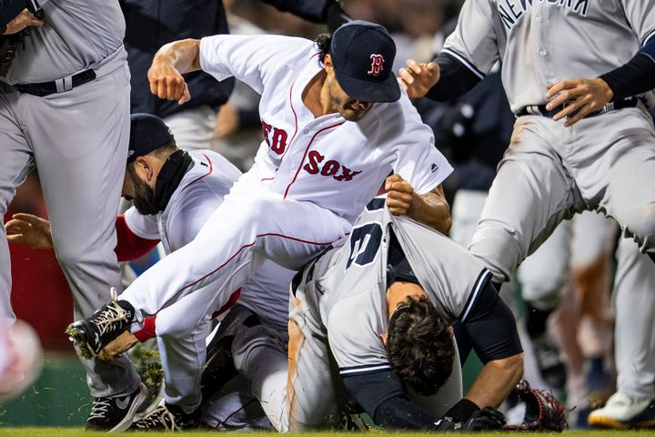 Joe Kelly #56 of the Boston Red Sox clenches his fist and grabs the jersey of Tyler Austin #26 of the New York Yankees.
