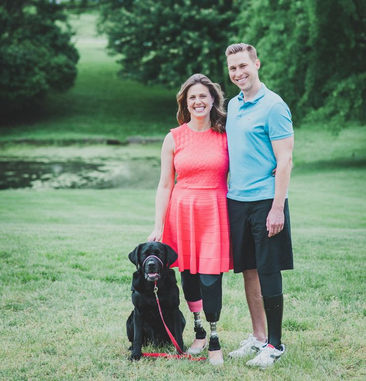 Jessica Kensky and Patrick Downes, who lost three legs between them in the blasts, pose with their support dog, Rescue.