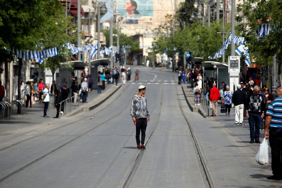 People stand still as a two-minute siren marking the annual Israeli Holocaust Remembrance Day is heard in Jerusalem on April