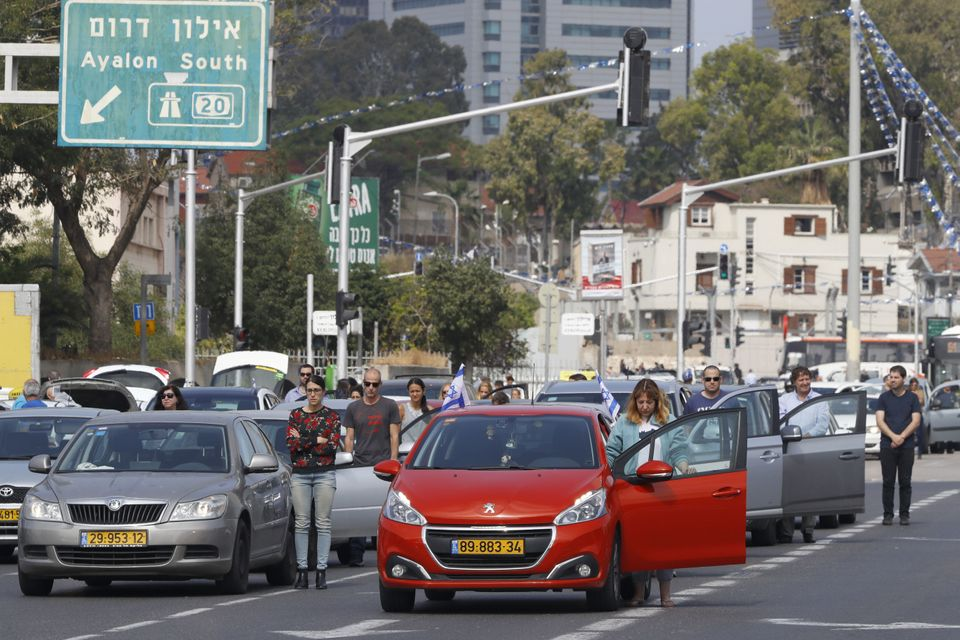 Drivers stop and stand in silence on a street in Tel Aviv on April 12, 2017, as sirens wailed across...