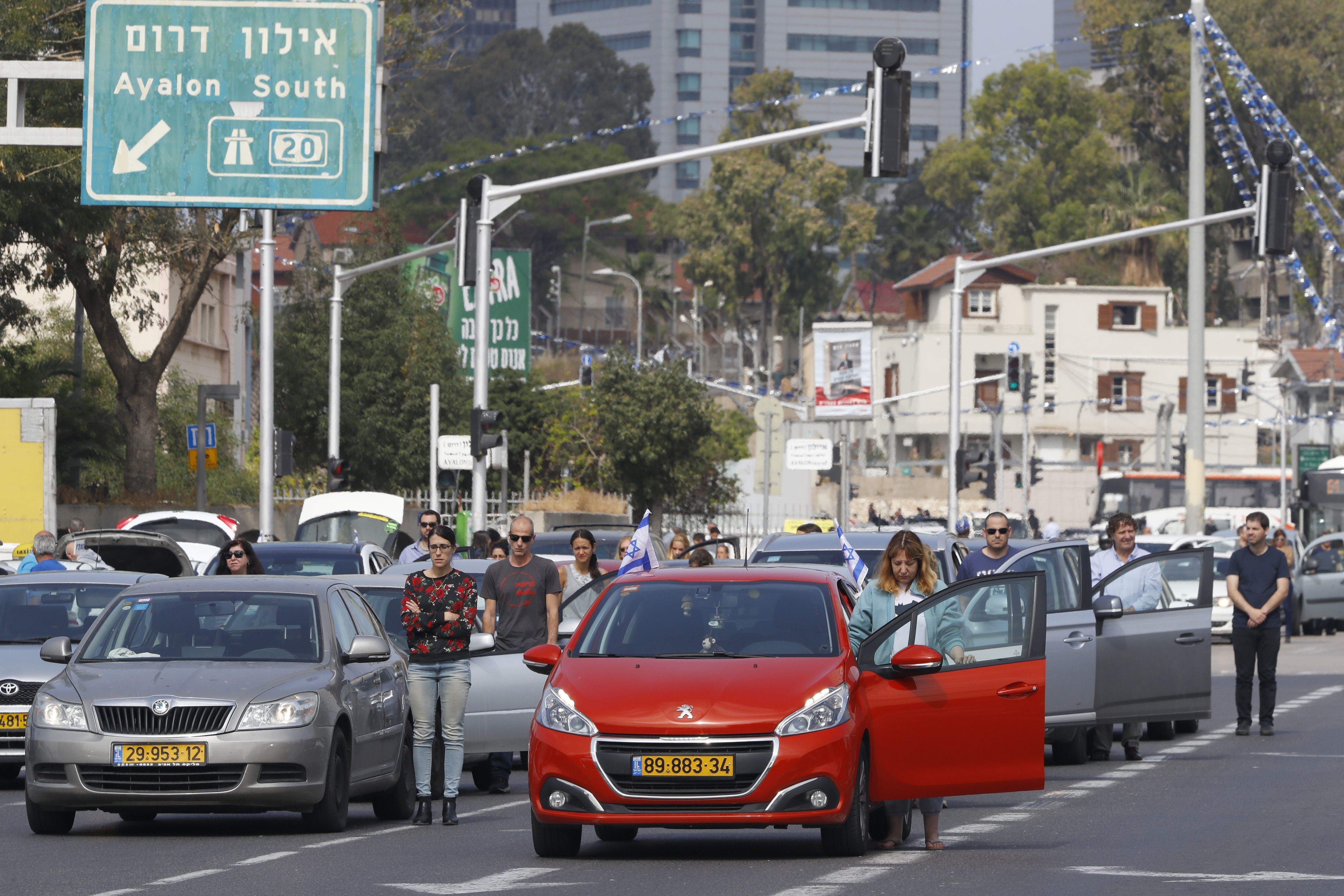 Drivers stop and stand in silence on a street in Tel Aviv on April 12, 2017, as sirens wailed across Israel for two minutes m