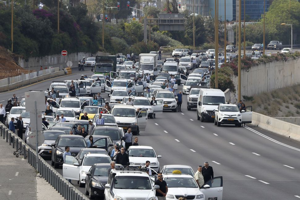 Drivers stop and stand in silence on a highway in Tel Aviv.