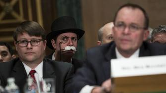 An attendee dressed as the 'Monopoly Man' listens during a Senate Banking, Housing & Urban Affairs Committee hearing with Mick Mulvaney, acting director of the Consumer Financial Protection Bureau (CFPB), in Washington, D.C., U.S., on Thursday, April 12, 2018. Senator Elizabeth Warren clashed with Mulvaney, accusing the former GOP congressman of putting politics ahead of protecting consumers. Photographer: Toya Sarno Jordan/Bloomberg via Getty Images