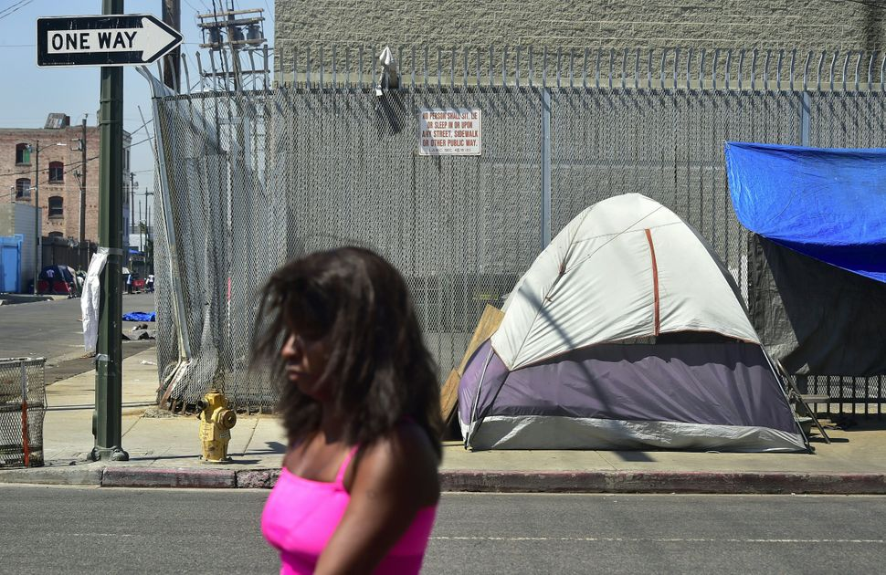 A woman walks past a sign posting the ordinance that led to the explosion of tents housing the homeless on Los Angeles s
