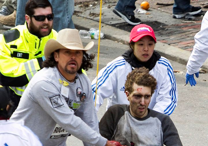 Carlos Arredondo, wearing a cowboy hat, and other people tend to survivor Jeff Bauman in the moments after the blas
