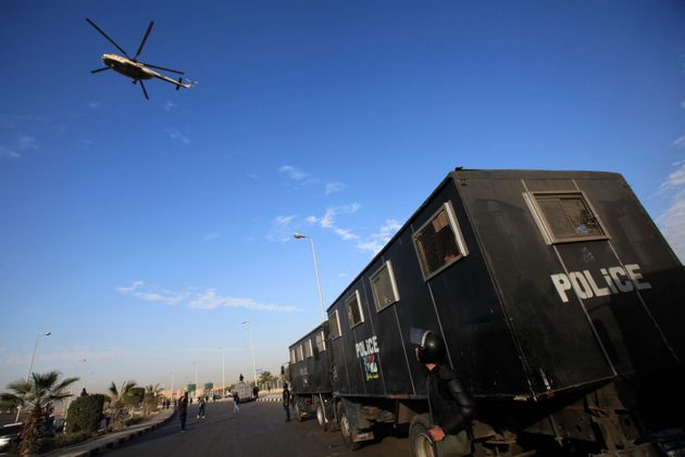 A military helicopter flies over riot police standing guard outside a police academy, where ousted Egyptian...