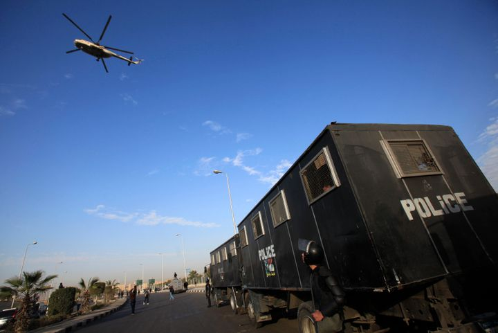 A military helicopter flies over riot police standing guard outside a police academy, where ousted Egyptian President Mohamed