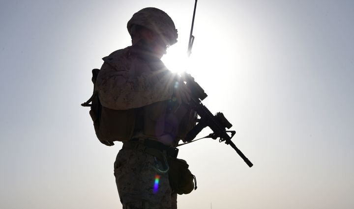A U.S. Marine watches Afghan Commandos take part in a combat training exercise at Shorab Military Camp in Helmand, Afghanista