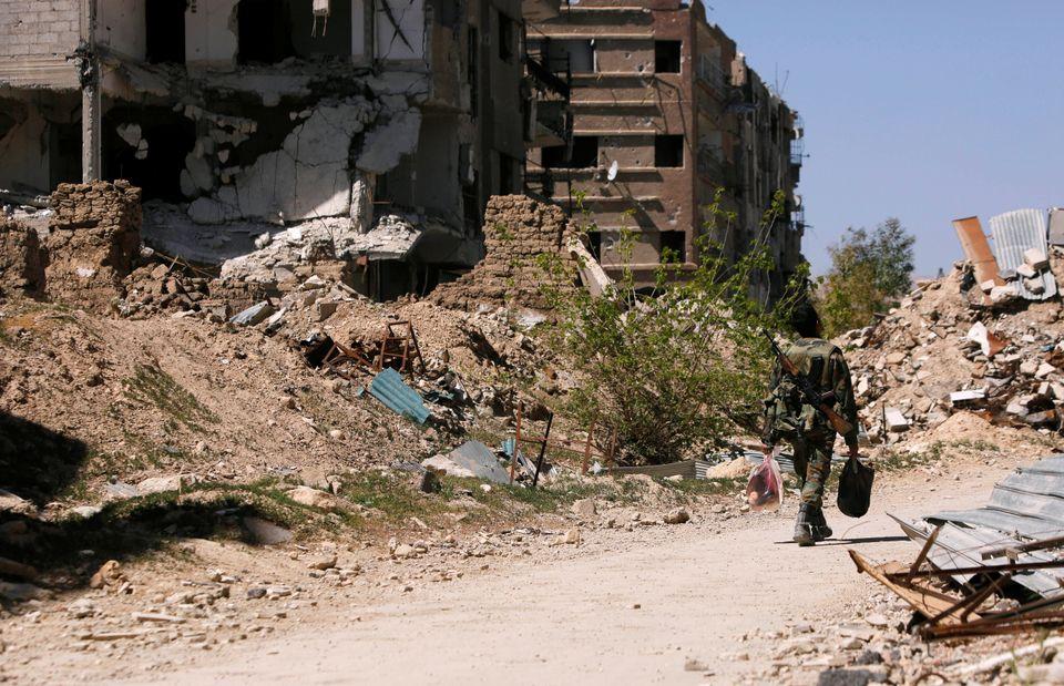 A member of Syrian forces of President Bashar al Assad walks past destroyed buildings in Jobar, eastern...