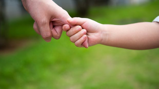 A child's hand holding  mother's hand.