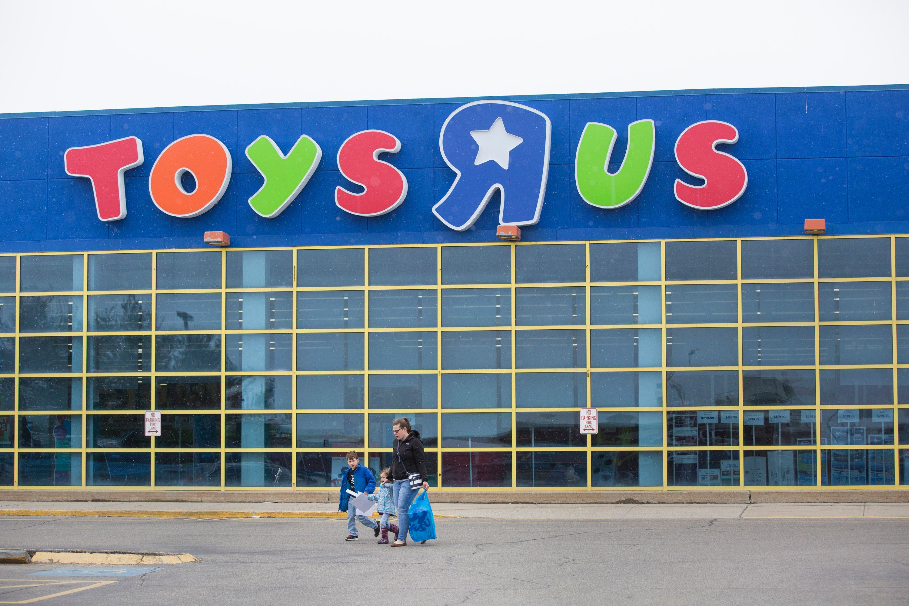 SOUTH PORTLAND, ME - MARCH 22: Vicki Brackley of Sabattus leaves Toys R Us on Thursday, March 22, 2018, with her children Declan, 7, and Sage, 3. She said they drove down to the South Portland store because they had gift cards to use and said she was disappointed that the liquidation sale that was supposed to start today had been postponed. (Photo by Derek Davis/Portland Press Herald via Getty Images)