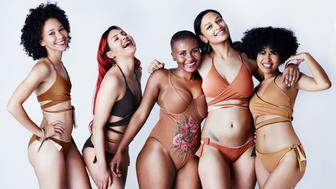 Studio shot of a group of beautiful young women in posing together in swimwear against a gray background