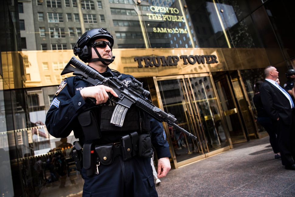 An armed police officer stands guard at the entrance of Trump Tower on April 13. Extra security measures at the building have