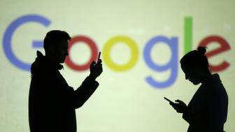 Silhouettes of mobile users are seen next to a screen projection of Google logo in this picture illustration taken March 28, 2018.  REUTERS/Dado Ruvic/Illustration