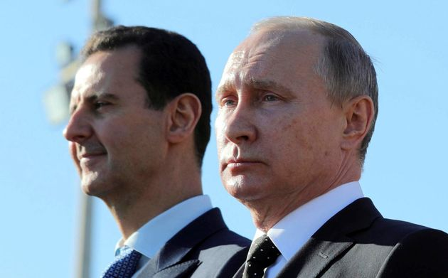 Russian President Vladimir Putin (R) and Syrian President Bashar al-Assad visit the Hmeymim air base...