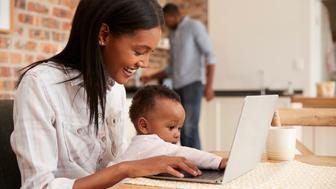 Mother And Baby Daughter Use Laptop As Father Prepares Meal
