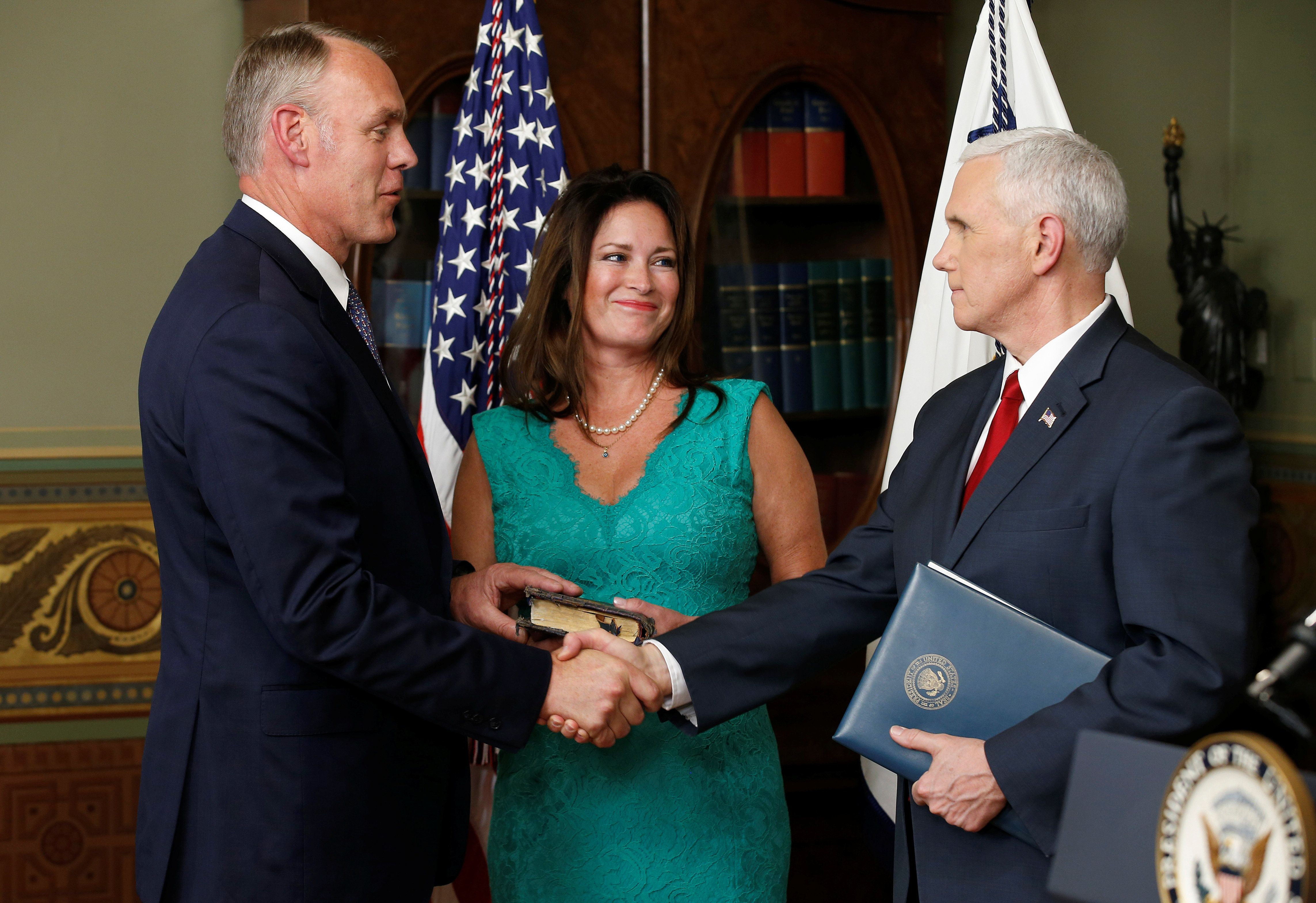 U.S. Vice President Mike Pence shakes hands with Ryan Zinke after Zinke was sworn in to be Secretary of the Interior as Zinke's wife Lolita watches, in Washington, U.S., March 1, 2017. REUTERS/Joshua Roberts