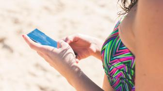 A woman with red nails uses her mobile phone on the beach during her summer holidays. Cadiz, Andalusia, Spain