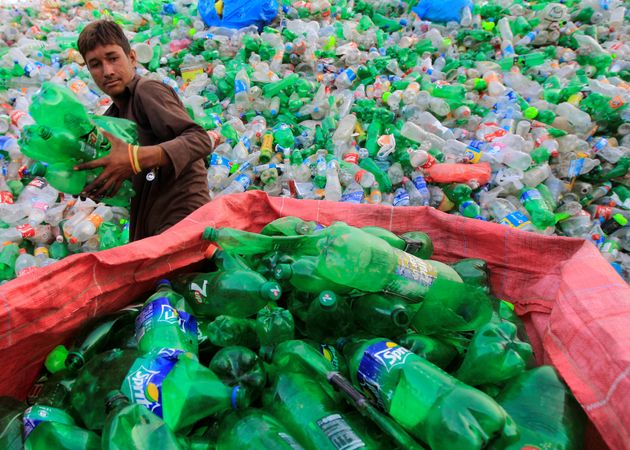 A worker sorts plastic bottles at a recycling workshop in Islamabad,