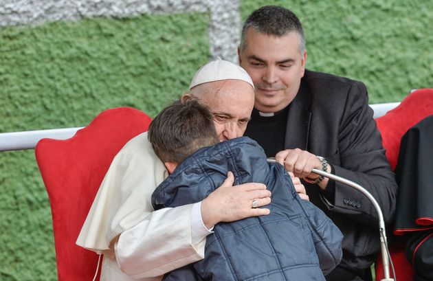 Pope Francis hugs a child named Emanuele at theSt. Paul of the Cross parish during a pastoral visit...