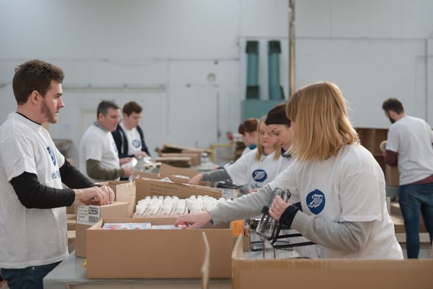 Volunteers packing wash bags in the Boots warehouse.