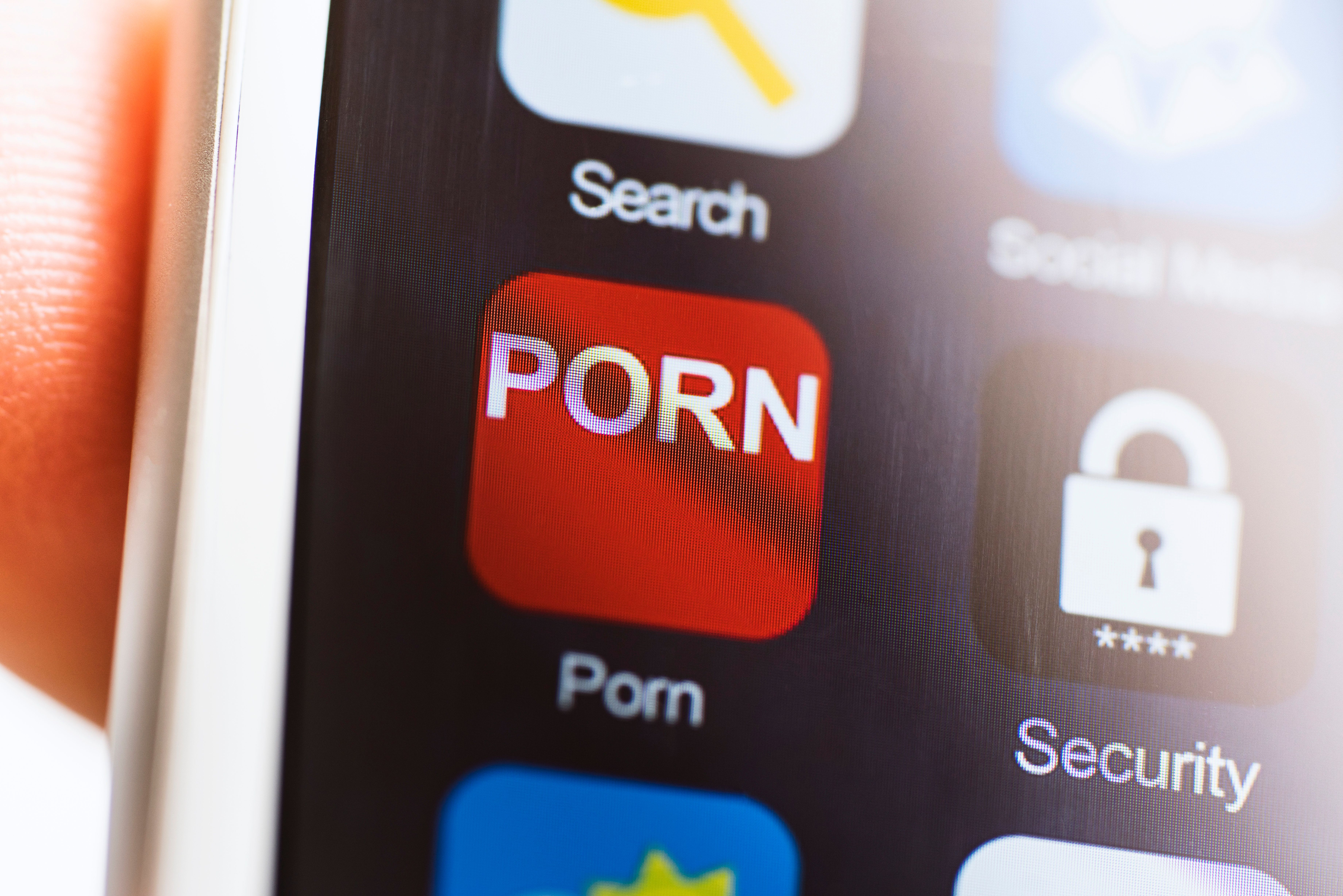 Hand holding phone, porn application icon on touchscreen.