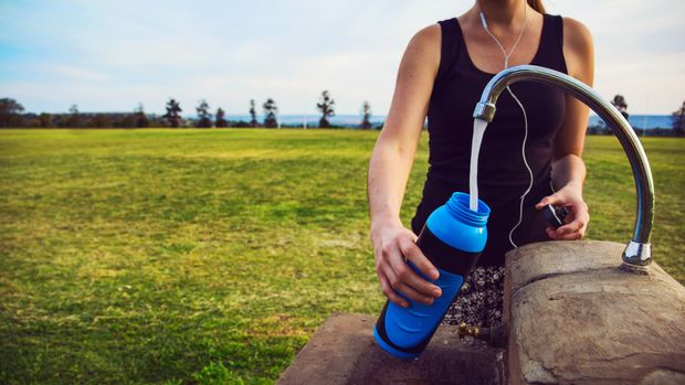 Female runner fills up water bottle outdoors at the public park