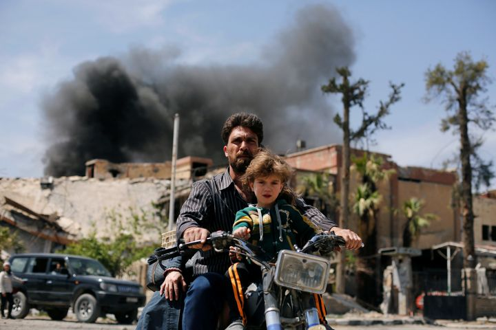 A man and a boy ride a motorbike at the city of Douma in Damascus, Syria, April 16, 2018.